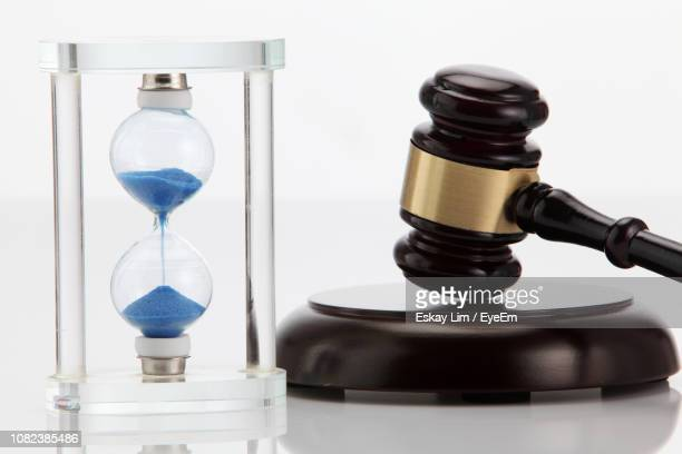 Close-Up Of Hour Glass And Mallet On White Background