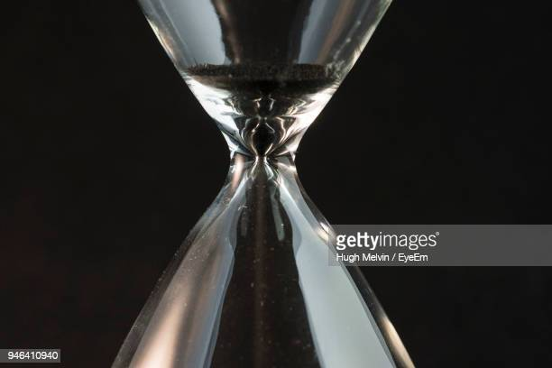 Close-Up Of Hourglass Against Black Background