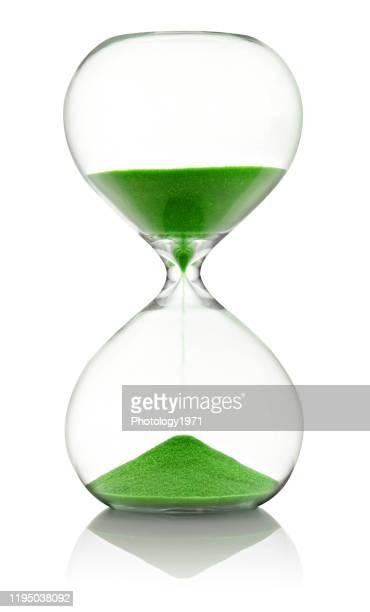 close-up of hourglass against white background - ampulheta imagens e fotografias de stock