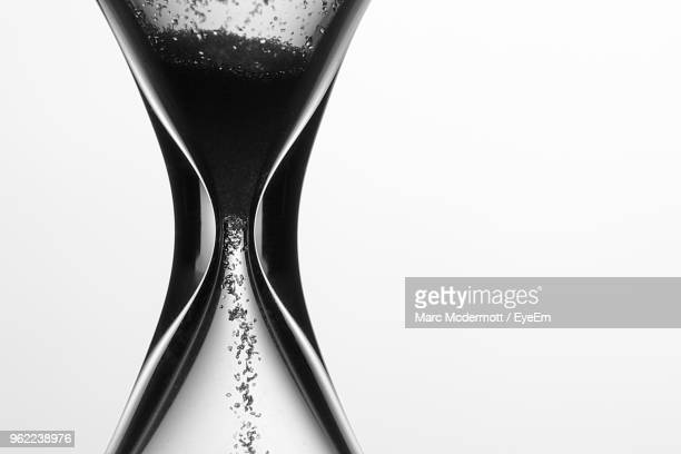 close-up of hourglass against white background - time stock pictures, royalty-free photos & images
