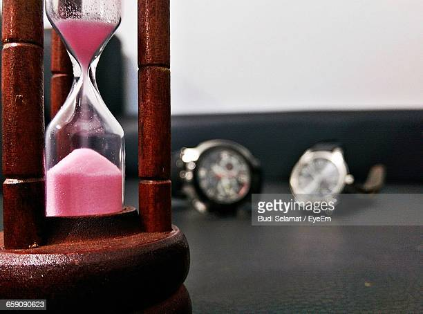 Close-Up Of Hourglass And Wristwatches On Table At Home