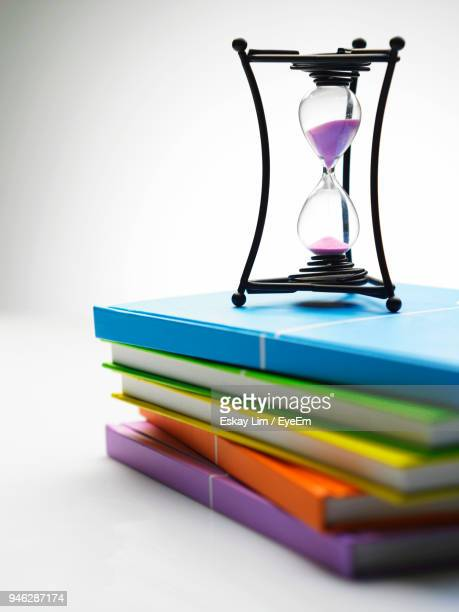 Close-Up Of Hourglass On Stacked Books Against White Background