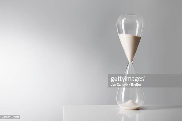 Close-Up Of Hourglass On Table Against Wall