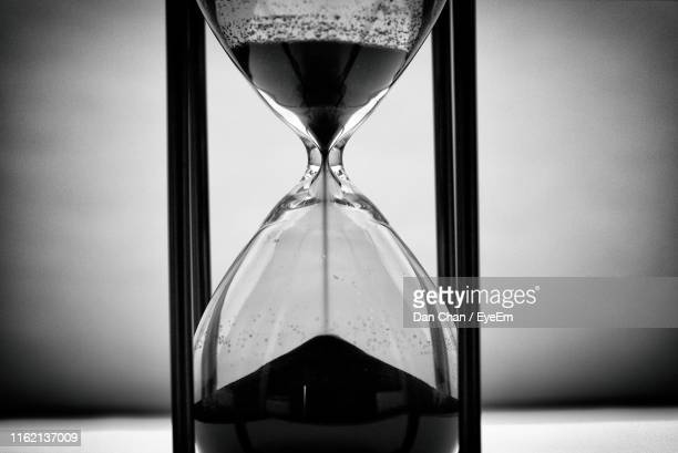 close-up of hourglass on table - hourglass stock pictures, royalty-free photos & images