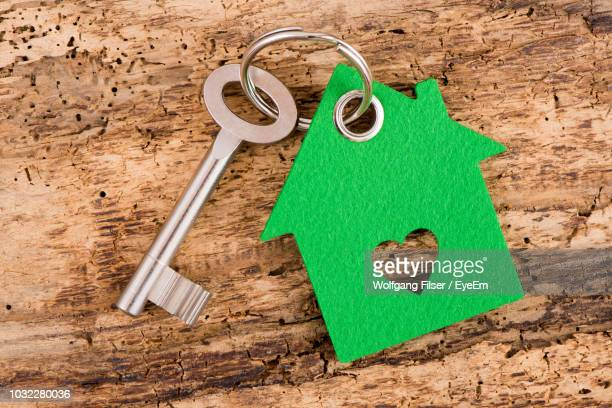 Close-Up Of House Key With Model Home On Wooden Table