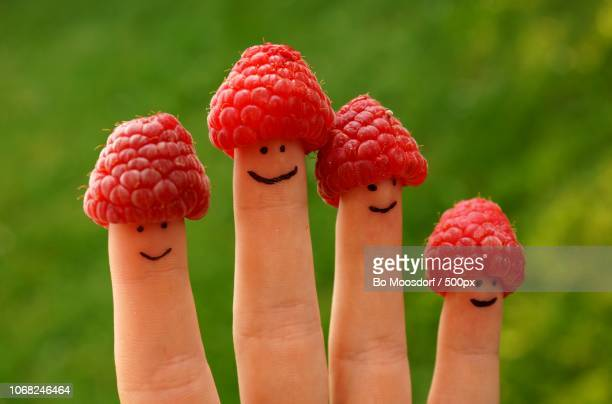 Close-up of human fingers with raspberries on top