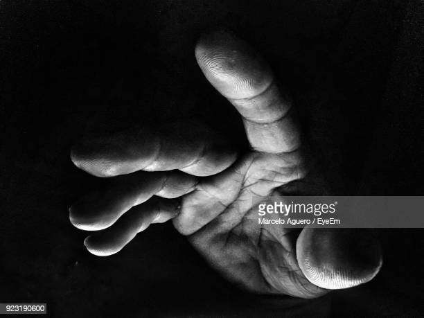 close-up of human hand against black background - black and white hands stock pictures, royalty-free photos & images