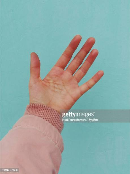 close-up of human hand against blue background - sleeve stock photos and pictures