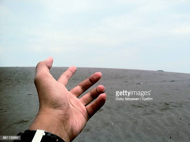 Close-Up Of Human Hand Against The Desert