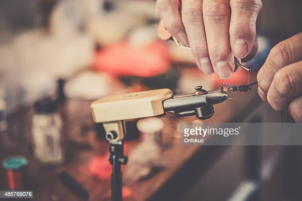 closeup of human hand creating fly fishing lure - fly casting stock pictures, royalty-free photos & images