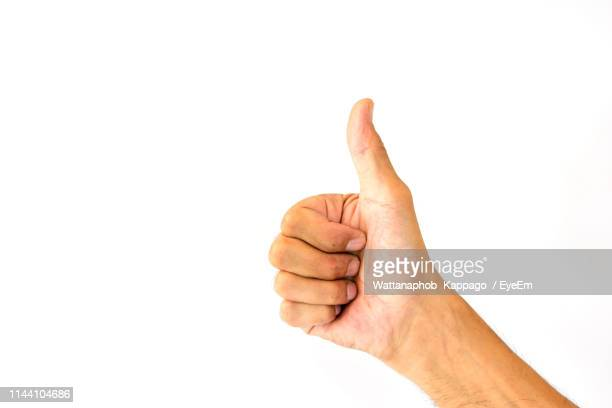 close-up of human hand gesturing thumbs up against white background - thumb stock pictures, royalty-free photos & images