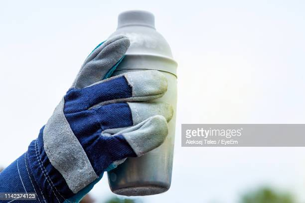 close-up of human hand holding bottle - mitten stock pictures, royalty-free photos & images