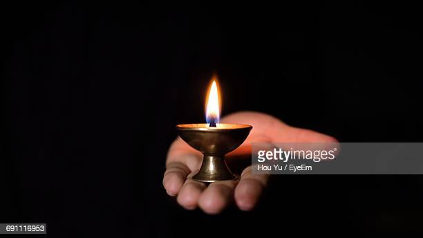 Close-Up Of Human Hand Holding Burning Candle
