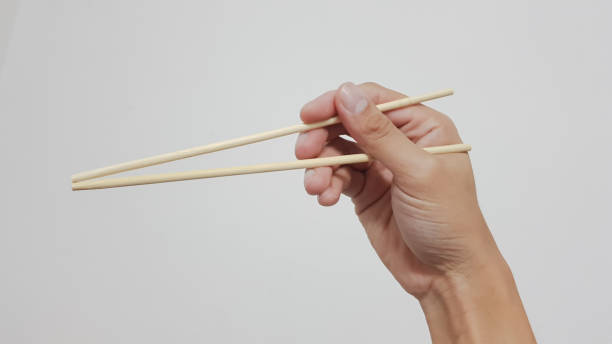 close-up of human hand holding chopsticks over white background - chop sticks stock pictures, royalty-free photos & images