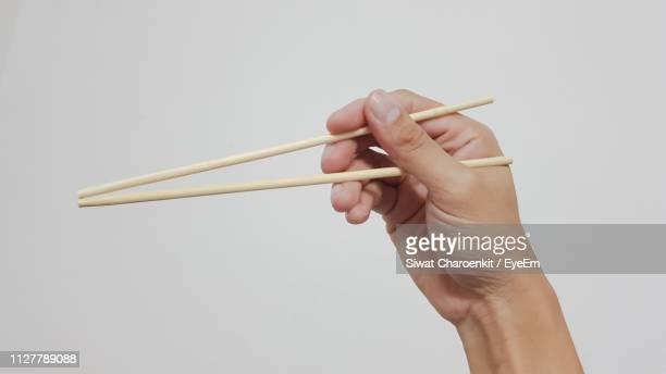 Close-Up Of Human Hand Holding Chopsticks Over White Background