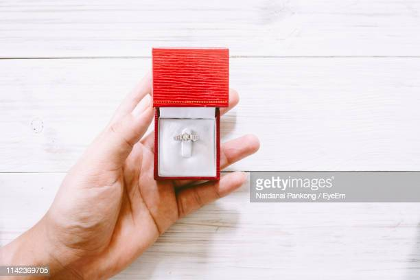 close-up of human hand holding diamond ring in jewelry box on table - 宝石箱 ストックフォトと画像