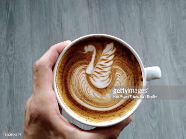 Close-Up Of Human Hand Holding Frothy Drink On Table