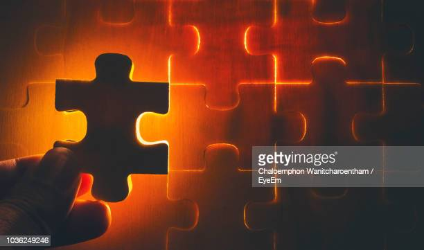 close-up of human hand holding illuminated puzzle - jigsaw piece stock pictures, royalty-free photos & images