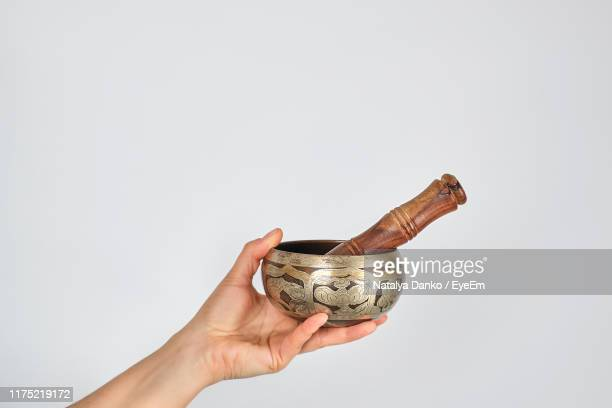 close-up of human hand holding singing bowl against white background - gong stock pictures, royalty-free photos & images
