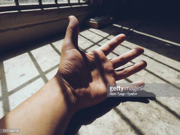 Close-Up Of Human Hand In Shadow Of Window