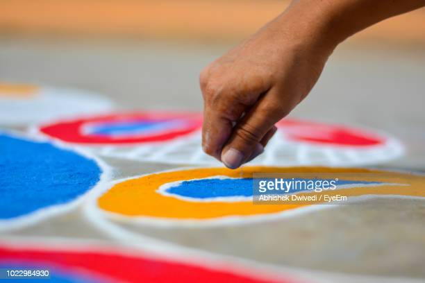 close-up of human hand making rangoli on footpath - rangoli stock pictures, royalty-free photos & images