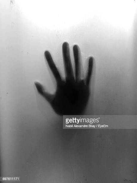 Close-Up Of Human Hand On Glass