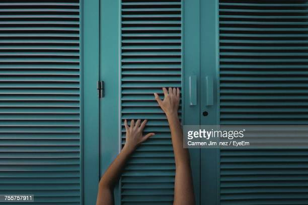 Close-Up Of Human Hand On Shutters