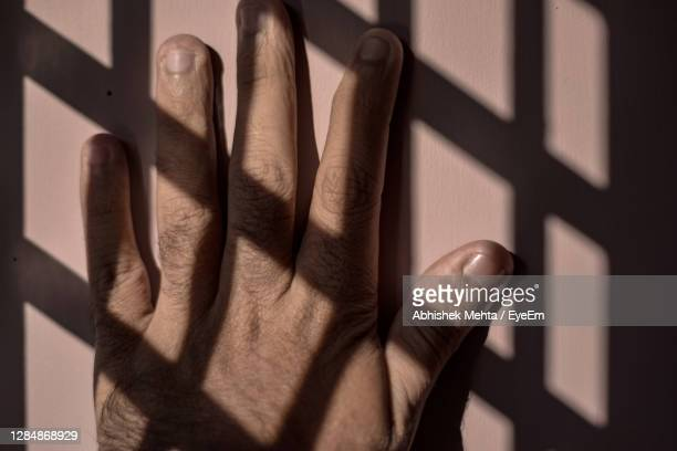 close-up of human hand on wall - prison stock pictures, royalty-free photos & images