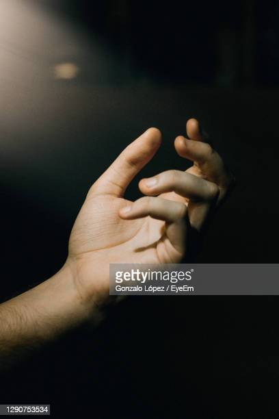 close-up of human hand over black background - colors soundtrack stock pictures, royalty-free photos & images
