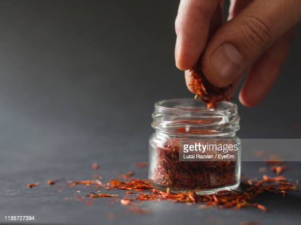 close-up of human hand removing saffron from bottle on table - lutai razvan stock pictures, royalty-free photos & images