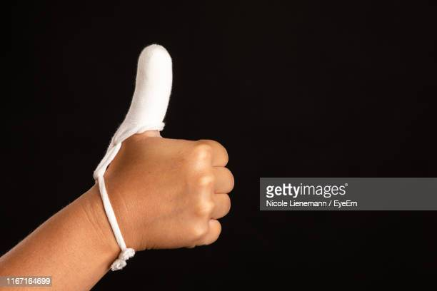 close-up of human hand showing thumbs up against black background - dedo humano fotografías e imágenes de stock