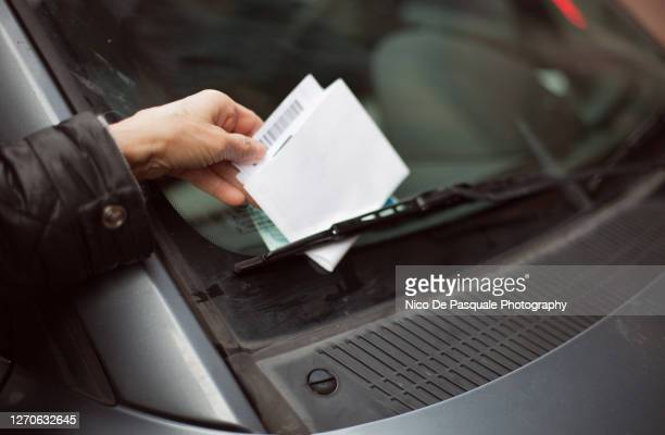 close-up of human hand taking parking ticket from car - ticket stock pictures, royalty-free photos & images