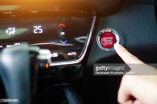close-up of human hand touching push button - hybrid car stock pictures, royalty-free photos & images