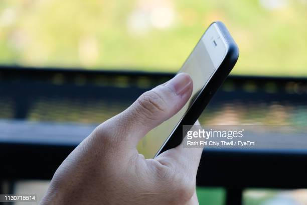 close-up of human hand using mobile phone by window - thumb stock pictures, royalty-free photos & images