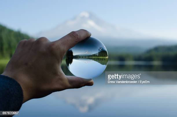 Close-Up Of Human Hand With Reflection Against Sky