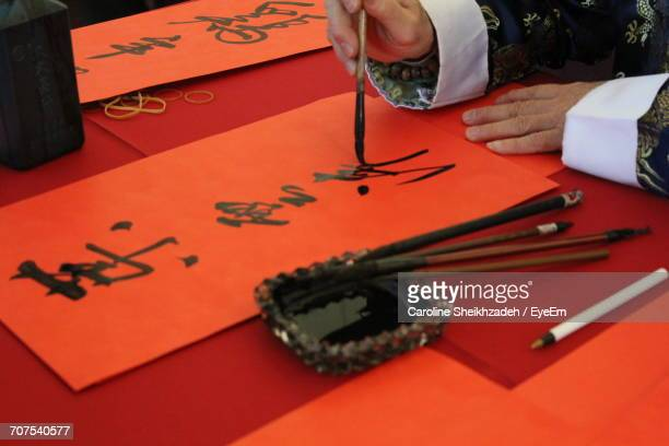 Close-Up Of Human Hand Writing Chinese Characters