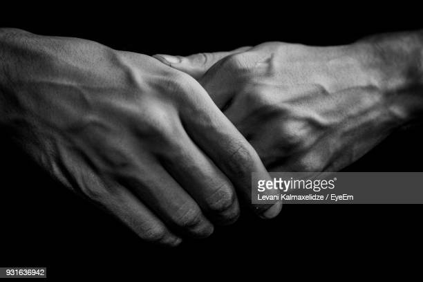 close-up of human hands against black background - black and white hands stock pictures, royalty-free photos & images