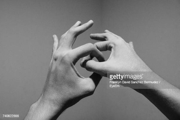 close-up of human hands against gray background - link chain part stock photos and pictures