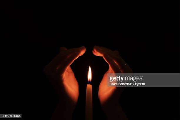 close-up of human hands covering candle flame against black background - laura cover stock pictures, royalty-free photos & images