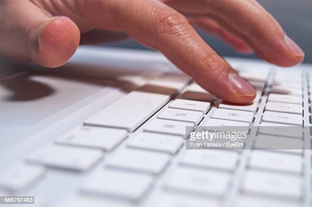 Close-Up Of Human Hands On Laptop