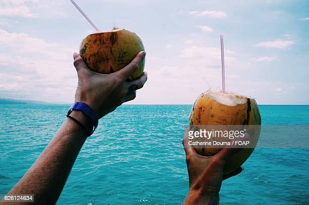 Close-up of human hand's showing coconuts against blue sky