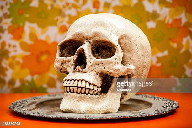 Close-up of Human Skull on Silver Plate with Floral Wallpaper