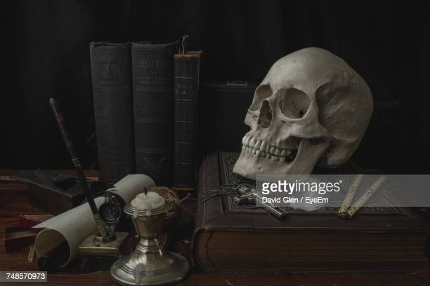 close-up of human skull with cross on book at table - human skull stock pictures, royalty-free photos & images