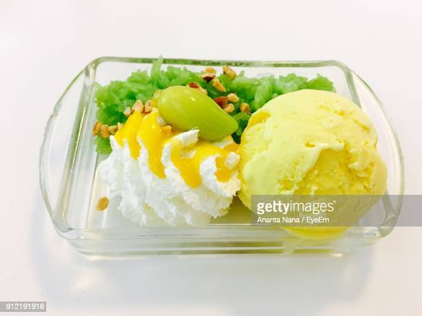 Close-Up Of Ice Cream In Container On White Table