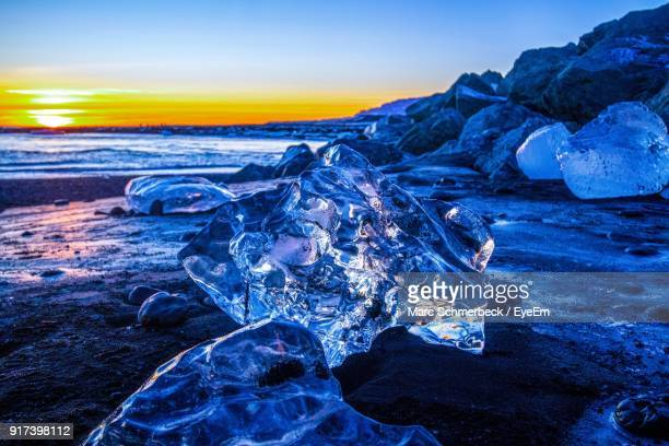 Close-Up Of Ice On Beach Against Sky