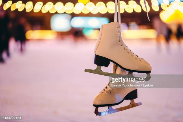 close-up of ice skates hanging in rink - ice skate stock pictures, royalty-free photos & images