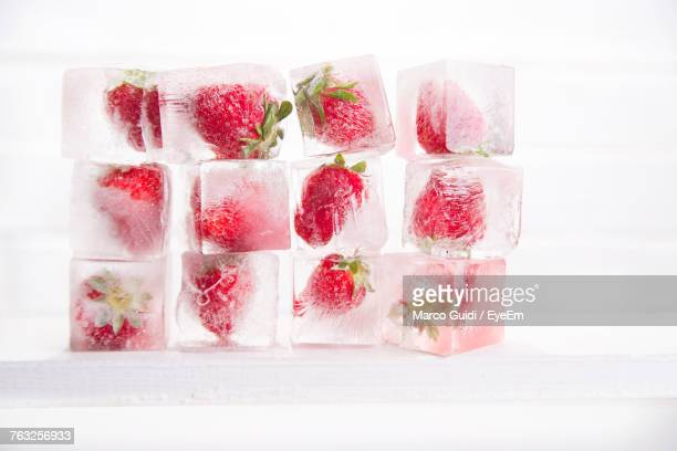 close-up of ice strawberries against white background - ice cube fotografías e imágenes de stock
