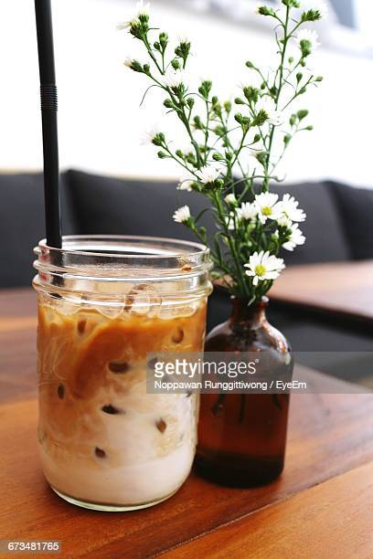 Close-Up Of Iced Coffee And Flower Vase On Table At Cafe