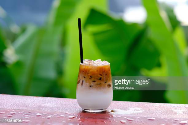 close-up of iced coffee cup on table outdoors . cafe latte . - koffie drank stockfoto's en -beelden