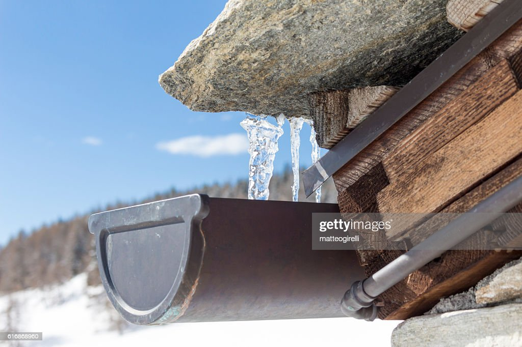 close-up of icicles on the eaves of a house : Stock Photo